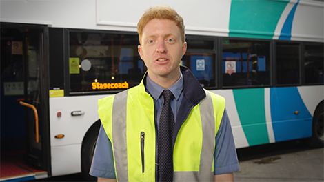 Presenter in front of bus